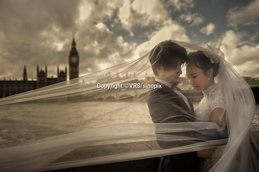 A Chinese couple pose for their wedding photos in London close to the Houses of Parliament and Big Ben, UK. . An increasing number of Chinese couple are having their wedding photos taken in the English country-side, classic towns and monuments to show in China.
