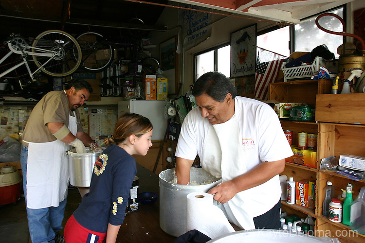 Mexican/Italian girl looks on as two Mexican American men work pots of masa with their hands at a family Tamalada (tamale making party), Torrance, CA