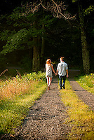 Young couple walking down driveway holding hands