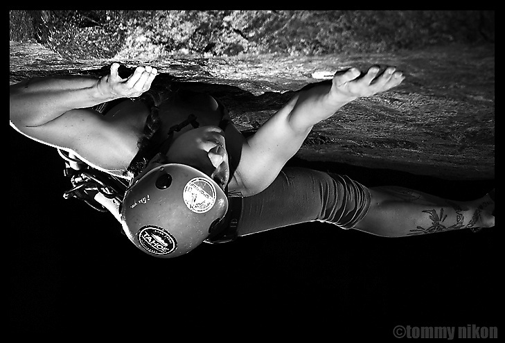 Female rock climber ascending sheer face