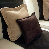 A detail of a living room showing the varying textures and tones of some knitted scatter cushions and a throw on the beige linen sofa