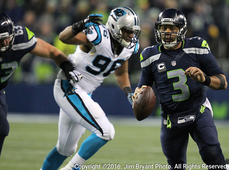 Seattle Seahawks quarterback Russell Wilson (3) scrambles away from Carolina Panthers defensive end Wes Horton (96) at CenturyLink Field in Seattle, Washington on December 4, 2016.  Wilson completed 26 of  36 passes for 277 yards and three for one touchdown and has one interception in the Seahawks 40-7 win over the Panthers.   ©2016. Jim Bryant photo. All Rights Reserved.