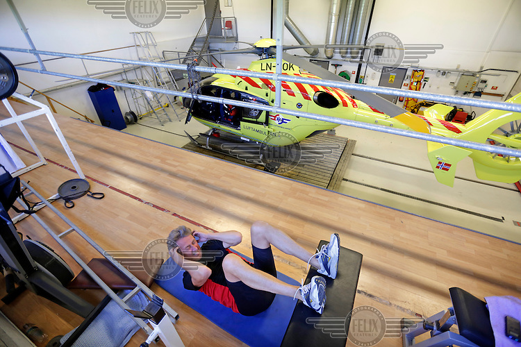 Rescue paramedic Asbjørn Møller working out in the hangar between missions. Norwegian Air Ambulance operating EC 135 helicopter out of their base in Trondheim, one of eight bases operated by the company.