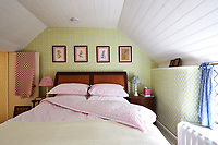 The traditionally styled guest bedroom is decorated in green and pink.