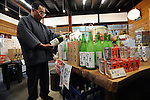 A customer looks at bottles of sake at the Tamagawa Sake Brewery in Kyoto, Japan. The traditional market for sake is literally dying off and the supply side is fading too, as old masters retire without a new generation to take over the brewing vats. More than 1,200 sake breweries exist in Japan, though falling domestic consumption has lead some to look to  overseas markets. Photographer: Robert Gilhooly