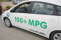 A side view of a plug-in hybrid Toyota Prius car with 'PLUG OK' license plate and stickers promoting CalCars.Org and 100+ MPG (miles per gallon). The depicted car has driven in a Step It Up 2007 protest rally calling for increased vehicle fuel efficiency to help reduce CO2 emissions related to global warming. San Francisco, California, USA
