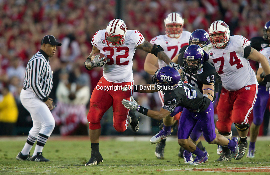 Wisconsin Badgers running back John Clay (32) stiff arms TCU Horned Frogs defensive back Jason Teague (27) during the 2011 Rose Bowl NCAA Football game in Pasadena, California on January 1, 2011. TCU won 21-19. (Photo by David Stluka)