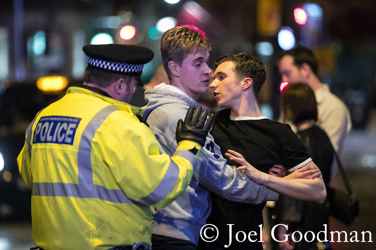 "© Joel Goodman - 07973 332324 . 17/12/2016 . Manchester , UK . A man holds his friend back in order to prevent a fight from escalating on Withy Grove . Revellers out in Manchester City Centre overnight during "" Mad Friday "" , named for being one of the busiest nights of the year for the emergency services in the UK . Photo credit : Joel Goodman"
