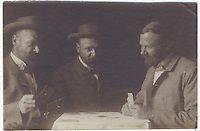 14b.<br /> <br /> 2 x 3 1/16 [sepia]<br /> <br /> 1 7/8 x 3 1/16 [sepia]<br /> <br /> double of Sam Crone, dressed similarly in each pose; playing cards at small table; frontal figure in jacket, playing card with right hand, wearing small bow tie, left; figure in profile in buttoned jacket, patiently waiting, holding card in left hand and poising right hand on table, right.