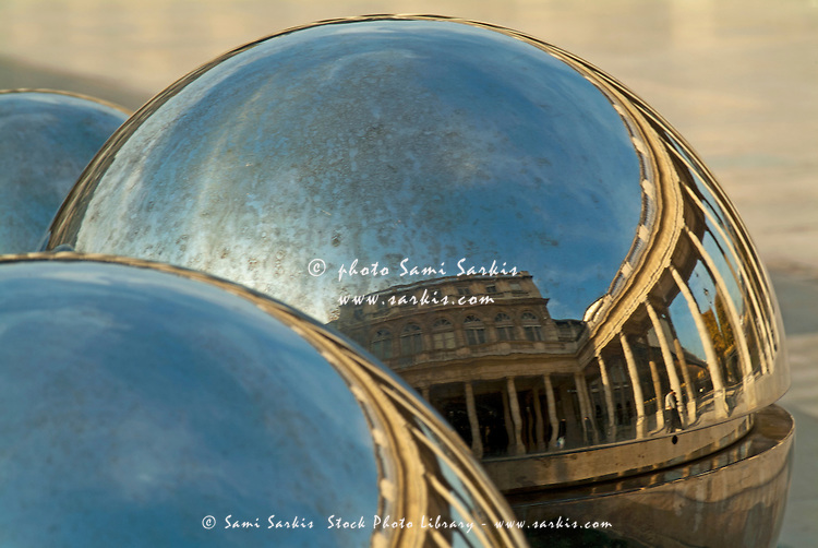 People and buildings reflected on the sphere sculpture within the gardens of the Palais-Royal, Paris, France.
