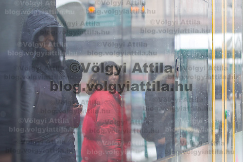 Pedestrian is reflected on the window of a tram in the snow fall in Budapest, Hungary on February 17, 2012. ATTILA VOLGYI