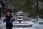 United States, New Jersey.  A parent walks with his soon through a park covered with snow after the pass of the nor'easter winter storm in Jersey City, New Jersey. 08/11/2012. Photo by Eduardo Munoz Alvarez / VIEWpress.