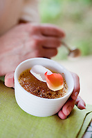 A ramekin filled with crème brûlée and topped with rose petals being enjoyed