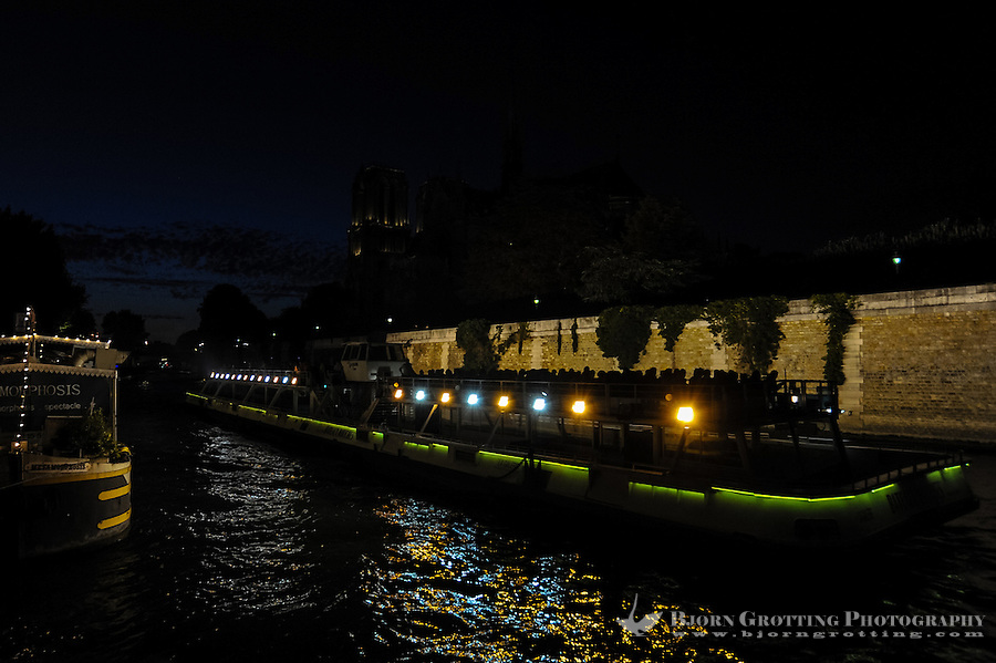 Paris, France. One of the many sightseeing boats on the river Seine passing the Notre Dame cathedral at night.