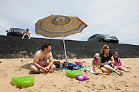 Andrew Crete (top left), 6, James Crete, Olivia Crete, 3, Karine Labelle, and Charlotte Crete, 9, (from left) sit near a recently-repaired section of the parking lot embankment at Herring Cove Beach in the Cape Cod National Seashore outside of Provincetown, Mass., USA, on Fri., July 1, 2016. Portions of the parking lot have been closed after land eroded during storms earlier this year. The family is visiting Cape Cod from Saint-Sauveur, Quebec, Canada.