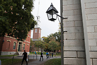 People walk through Harvard Yard at Harvard University in Cambridge, Massachusetts, USA, on Mon., Oct 15, 2018. The steeple of Memorial Church is seen in the rear.