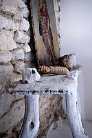 Detail of a rustic wooden console table displaying a painting and sculpture against a bare stone wall