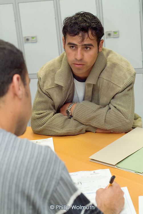 A newly arrived Iraqi Kurdish refugee speaks with an interpreter during an interview at the Migrant Helpline Induction Centre in Dover. The interview determines elegibility for housing and financial support by the National Asylum Support Service (NASS).