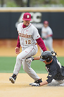 John Sansone (12) of the Florida State Seminoles applies a tag to Evan Stephens (5) of the Wake Forest Demon Deacons as he tries to steal second base at Wake Forest Baseball Park on April 19, 2014 in Winston-Salem, North Carolina.  The Seminoles defeated the Demon Deacons 4-3 in 13 innings.  (Brian Westerholt/Four Seam Images)