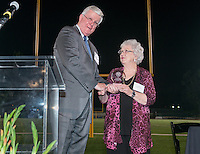 Sally Barnes Leach accepts the Athletics Hall of Fame award for John Barnes '52 from James Dennis '66. Alumni, family, staff and students at the Occidental College Athletics Hall of Fame event, part of Homecoming weekend, Oct. 24, 2014 on Patterson Field. (Photo by Marc Campos, Occidental College Photographer)