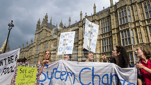 A group of demonstrators hold placards and a banner which says 'System Change' in front of the Houses of Parliament during the Climate Change demonstration, London, 21st September 2014. © Sue Cunningham