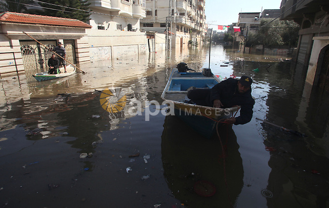 Palestinian rescue workers help residents move on a boat in Gaza City, Dec. 21, 2013. Rescue workers evacuated thousands of Gaza Strip residents from homes flooded by heavy rain, using fishing boats and heavy construction equipment to pluck some of those trapped from upper floors. Photo by Yasser Qudih