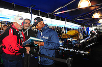 Feb. 26, 2011; Pomona, CA, USA; NHRA top fuel dragster driver Antron Brown (right) signs autographs for fans during qualifying at the Winternationals at Auto Club Raceway at Pomona. Mandatory Credit: Mark J. Rebilas-.
