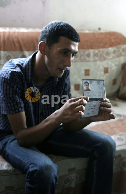 Ahmed Obaid, 18, a mentally disabled Palestinian youth, shows his ID and his mental disability card at their home in Issawiya neighborhood in Jerusalem on 02 September 2013. Israeli security forces arrested Obaid during a protest against killing of three Palestinians in Qalandiya refugee camp. He was released on bail on Monday after spending a week in jail under torture. Photo by Saeed Qaq