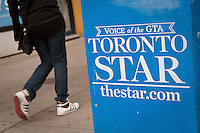 A woman walks by a Toronto Star newspaper box in Toronto April 24, 2010. Owned by Toronto Star Newspapers Ltd., a division of Star Media Group, a subsidiary of Torstar Corporation, The Toronto Star is Canada's highest-circulation newspaper.