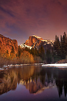 799451195 winter sunset turns snow-capped half dome golden with its reflection in the merced river with its banks also covered in snow yosemite national park california