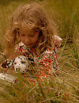 Girl,8, with blond, light-brown hair, sitting in tall grass holding a puppy dalmation.