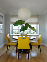 In this dining room bright yellow dining chairs surround a pedestal table