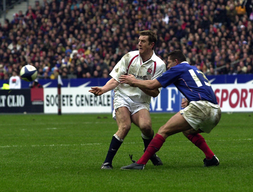 Photo.Richard Lane.France v England at Stade de France. 2-3-2002. Lloyds TSB Six Nations Championship..Will Greenwood gets the ball away as Tony Marsh tackles.