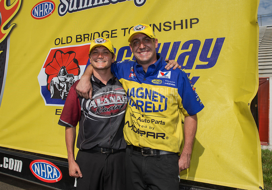 Jun. 2, 2013; Englishtown, NJ, USA: NHRA crew member Alex Conaway for Matt Hagan and a crew member for Shawn Langdon celebrate together after winning the Summer Nationals at Raceway Park. Mandatory Credit: Mark J. Rebilas-