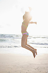 USA, Florida, St. Pete Beach, Girl (8-9) in bikini jumping on beach