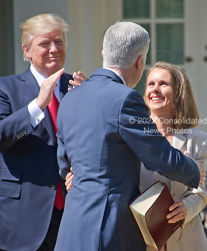 Associate Justice of the United States Supreme Court Neil Gorsuch hugs his wife Louise after taking the Oath of Office from Associate Justice Anthony Kennedy in the Rose Garden of the White House in Washington, DC on Monday, April 10, 2017.  US President Donald J. Trump applauds at left.<br /> Credit: Ron Sachs / CNP<br /> (RESTRICTION: NO New York or New Jersey Newspapers or newspapers within a 75 mile radius of New York City)