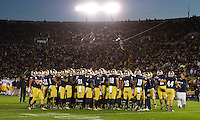 The Irish huddle up as the sun sets behind Notre Dame Stadium for the night game against USC.