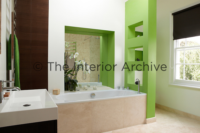 A modern white bathroom with vibrant green accent colour. A mirror is set in a recess behind a bath at the foot of which stands a shelving wall
