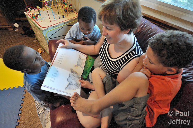 Elaine Stellini reads a book while her son Kayden, 3, observes from the front. Sam, 4, on her right, and Zachary, 6, also share the story. Stellini lives with her lesbian partner Barb and the three boys in Vancouver, Washington. The family is active in Vancouver Heights United Methodist Church, a reconciling congregation.