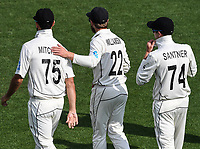 30th November 2019, Hamilton, New Zealand;  Kane Williamson gives Daryl Mitchell a tap on the shoulder as Mitchell Santner looks on during play on day 2 of 2nd test match between New Zealand and England,  International Cricket at Seddon Park, Hamilton, New Zealand.  - Editorial Use