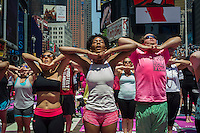 """Thousands of yoga practitioners pack Times Square in New York to participate in a mid-day Bikram Yoga class on the first day of summer, Friday, June 21, 2013. The 11th annual Solstice in Times Square, """"Mind Over Madness"""",  stretches the yogis' ability to block out the noise and the visual clutter that surround them in the Crossroads of the World"""". (© Frances M. Roberts)"""