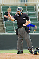 Home plate umpire Cody Oakes makes a strike call during the South Atlantic League game between the Greensboro Grasshoppers and the Kannapolis Intimidators at CMC-Northeast Stadium on July 12, 2013 in Kannapolis, North Carolina.  The Grasshoppers defeated the Intimidators 2-1.   (Brian Westerholt/Four Seam Images)