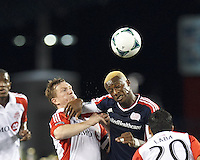 New England Revolution forward Dimitry Imbongo (92) attempts to control the ball as Toronto FC defender Steven Caldwell (13) pressures. In a Major League Soccer (MLS) match, Toronto FC (white/red) defeated the New England Revolution (blue), 1-0, at Gillette Stadium on August 4, 2013.