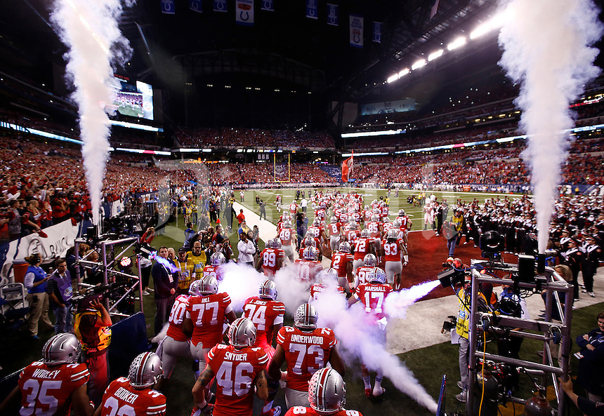The Ohio State Buckeyes run on to the field before the Big Ten Championship game between the Ohio State Buckeyes and the Wisconsin Badgers at Lucas Oil Stadium in Indianapolis, Saturday night, December 6, 2014. (The Columbus Dispatch / Eamon Queeney)