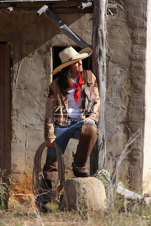 A Spanish or Native American Indian cowgirl in front of a stucco building