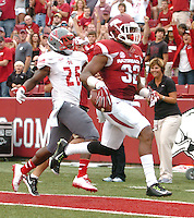 NWA Media/ANDY SHUPE - Arkansas Jonathan Williams (32) carries the ball into the end zone ahead of Nicholls defensive back B.T. Sanders during the second quarter Saturday, Sept. 6, 2014, at Razorback Stadium in Fayetteville