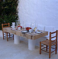 A large stone table and a bench built-in to a whitewashed wall of the patio has been laid for dinner