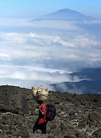 A porter carries trekkers' gear up Mt. Kilimanjaro, near Moshi in northern Tanzania, June 5, 2004. Mt. Meru looms in the background. Tourists pay more than $750 to be guided on six and seven-day treks leading to the Kilimanjaro's Uhuru peak, the highest point in Africa at 19, 340 feet (5985 meters). Many but not all make it usually as a result of the effects of altitude.(Rick D'Elia)<br />