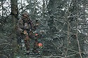 00105-043.12 Bowhunting (DIGITAL) Archer is in tree stand in balsam fir during snow storm.  Hunt, cold, late season, deer, winter.  H4R1
