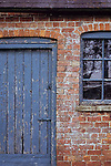 Detail of old orange brick stable block or barn with flaking blue painted wooden door and windows and slate roof